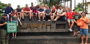 A group of around 20 students pose with two professors around the EARTH University sign. Some are Colorado State University students, and they wear green bandanas. Some are EARTH University students, and they wear orange bandanas. All are smiling.