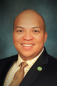 Headshot of Dr. Rodolfo Valdez-Vasquez, a smiling man with a bald head and brown eyes. He is wearing a suit and a pin with the Colorado State mascot, Cam the Ram, on his lapel.