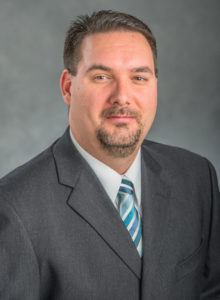 Photo of James Lucas, a middle-aged man with brown hair and a goatee, wearing a gray suit with a blue striped tie.
