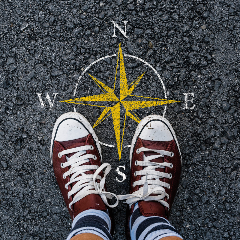 The shoes of a young adult standing on a compass drawn on the ground