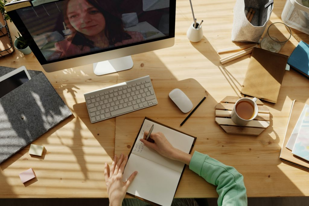 View from above desk showing person's arms, writing in a notebook, in front of a screen during a virtual meeting